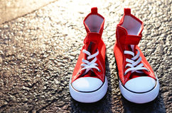 Pair of red trainers on asphalt Royalty Free Stock Images