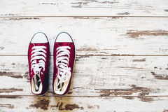 Pair of red trainers on wooden floor top view Stock Image