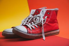 Pair of red used sneakers on colorful background, view from side royalty free stock photo