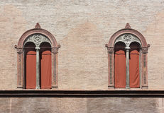Pair of Renaissance Windows in Bologna, Italy. Ornate pair of Renaissance windows with terracotta surrounds on a pale pink brick wall Royalty Free Stock Photography