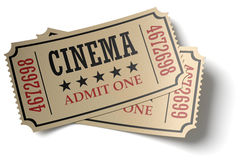 Pair of retro cinema tickets with shadows. Vintage retro cinema creative concept: pair of retro vintage cinema admit one tickets made of yellow textured paper Royalty Free Stock Images