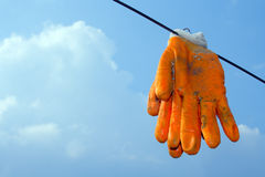 Pair ribbon gloves hanging on the rope over sky. Pair ribbon orange gloves hanging on the rope over sky Royalty Free Stock Images