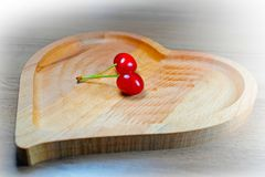 Pair of ripe sweet cherry berries in heart-shaped wooden bowl royalty free stock photos