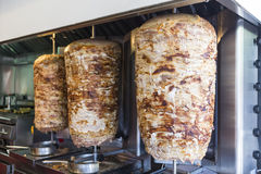 A pair of rotating skewered chicken and lamb meat grilled and re Stock Image