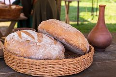Pair of round rye bread rustic fresh appetizing in a wicker basket with a clay vessel of wine a light lunch of the Middle Ages stock photos