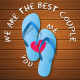 A pair of rubber flipflops on a wood panel Stock Photo