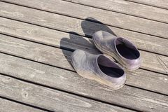 Pair rubber galoshes stand on wooden boards stock photos