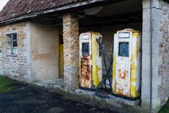 A pair of rusting old yellow petrol pump. A pair of rusting old single yellow petrol pump, with a large dial showing gallons, inside a small open building royalty free stock photo