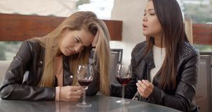 Pair of sad women drinking wine. Devastated friend with head in her arms while sitting with friend drinking wine outdoors stock video footage