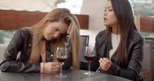 Pair of sad women drinking wine stock video footage