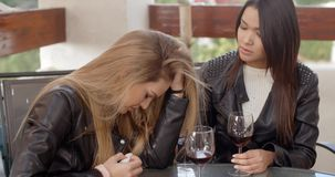 Pair of sad women drinking wine. Devastated friend with head in her arms while sitting with friend drinking wine outdoors stock video