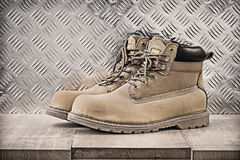 Pair of safety boots wooden board channeled metal sheet construc. Tion concept royalty free stock image