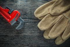 Pair of safety gloves plumbing monkey wrench on wooden board.  Stock Image