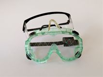 Pair of safety goggles. Two varieties of protective eyewear displayed. Green flexible plastic with eye vents, and hard plastic wrap around glasses with black rim