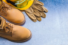 Pair of safety lace boots leather gloves hard hat and working go Royalty Free Stock Images