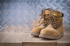Pair of safety lace boots wooden board fluted metal sheet constr. Uction concept Stock Images