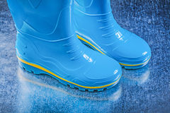 Pair of safety rubber boots on metallic background gardening con Royalty Free Stock Photos