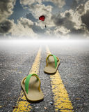 A pair of sandal on the road with parachute on the sky Royalty Free Stock Photos