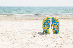 Pair of sandals in sand beach Stock Images