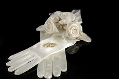 A pair of satin gloves with wedding rings. On the black background stock photo