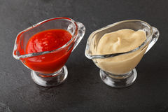 Pair sauceboats with condiment. Closeup of two glass sauce-boats with  ketchup and mustard on black rough slate plate Royalty Free Stock Image