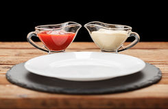 Pair of sauceboats and empty plate Royalty Free Stock Image
