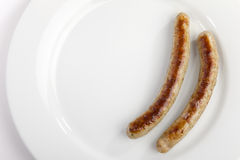 A pair of sausages on a plate Royalty Free Stock Images
