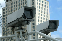 Pair of security cameras. Atop a high structure Stock Photos
