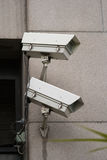 Pair of security cameras. Mounted to side of building stock photos