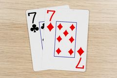 Pair of sevens 7 - casino playing poker cards. Pair of sevens 7 - winning hand of gambling casino poker playing cards on a table stock images