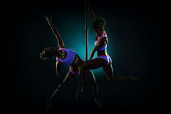Pair of sexy pole dancers under UV light. Image of sexy pole dancers under UV light Stock Image