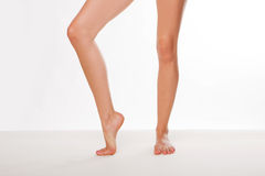 Pair of womans legs. Pair of bare womans legs with one foot raised up on tip toe and one flat on the ground on a white background stock image
