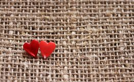 A pair of sharp pins in the form of red hearts stuck in the roug Stock Photos