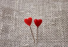 Pair of sharp pins in the form of red hearts stuck in the rough Royalty Free Stock Photography