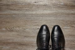 Top view of a pair of men`s shoes on a wooden floor. A pair of shined, black, cap toed oxford shoes on a wooden floor, room for text stock photo