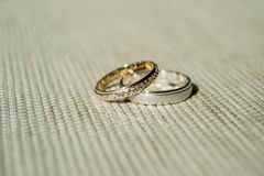Gold and silver wedding rings over clear and rough surface. Light background and sunlight. Shadows marked. 02. stock photography