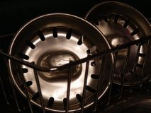 Kitchen Sink Plug. A pair of shiny stainless kitchen sink plugs stock photography
