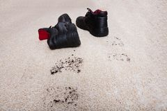 Pair Of Shoes With Mud On Carpet Floor. High Angle View Of A Pair Of Shoes With Mud Lying On Carpet Floor Stock Image