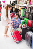 Pair in shop choosing suitcase Royalty Free Stock Photography