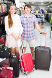 Pair in shop choosing suitcase. Smiling pair shops at the store choosing suitcase. Focus on man Royalty Free Stock Image