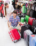 Pair in shop choosing suitcase. Smiling young pair shops at the store choosing suitcase Royalty Free Stock Photo