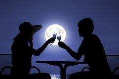 The pair silhouette is held by goblet with wine. On a moon night Stock Photo