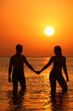 Pair silhouette keeps for hands in sea on sunset. Background Royalty Free Stock Photography