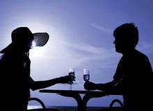 Pair silhouette sit at a table and hold goblets Royalty Free Stock Image
