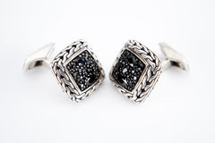 Pair of silver cuff links over white. Cufflinks with Black Sapphire Stock Image