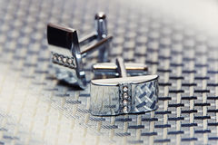 Pair of silver cuff links on the man's tie Stock Image