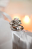 Pair of silver wedding rings. On silky material with candle burning in background Royalty Free Stock Images
