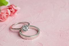 A pair of silver wedding rings. On a pink textured surface with copy space for your text in the background stock photo