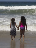 A Pair of Sisters Brace for an Oncoming Wave Royalty Free Stock Images
