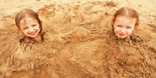 A Pair of Sisters Buried in the Sand Stock Images